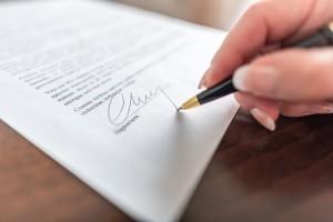 Iemand ondertekent een juridisch document.